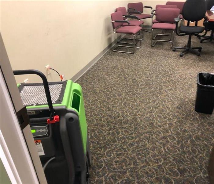 office confence room with wet carpet and a dehumidifier placed for druing