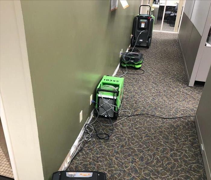 Commercial office with cubicles and green fans and dehumidifiers set out drying the carpte