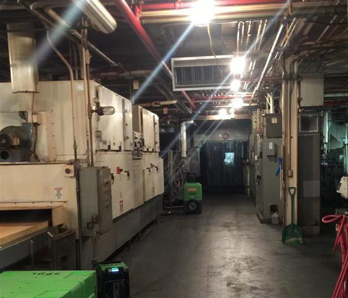 A manufactoring facility hallway with dry ground and one remaining piece of drying equipment